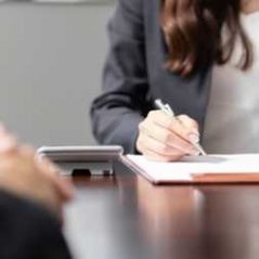 Conveyancer making notes in meeting